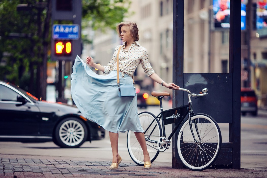 darya kamalova a fashion blogger from thecablook in dallas texas on the bycicle in polka dot shirt and blue skirt with gold espadrilles and other storie bag for rewardstyle rsthecon-10 copy