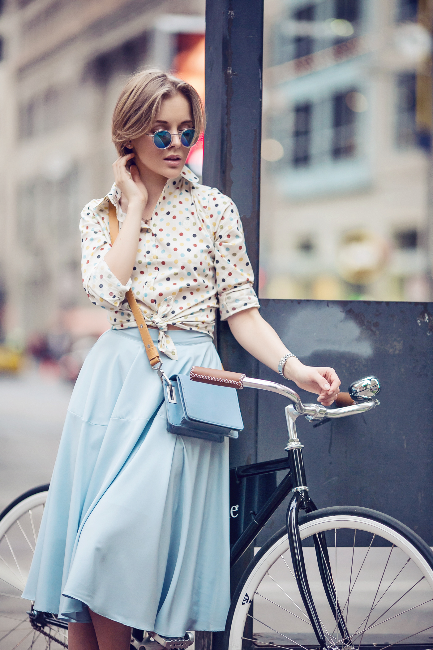 darya kamalova a fashion blogger from thecablook in dallas texas on the bycicle in polka dot shirt and blue skirt with gold espadrilles and other storie bag for rewardstyle rsthecon-13