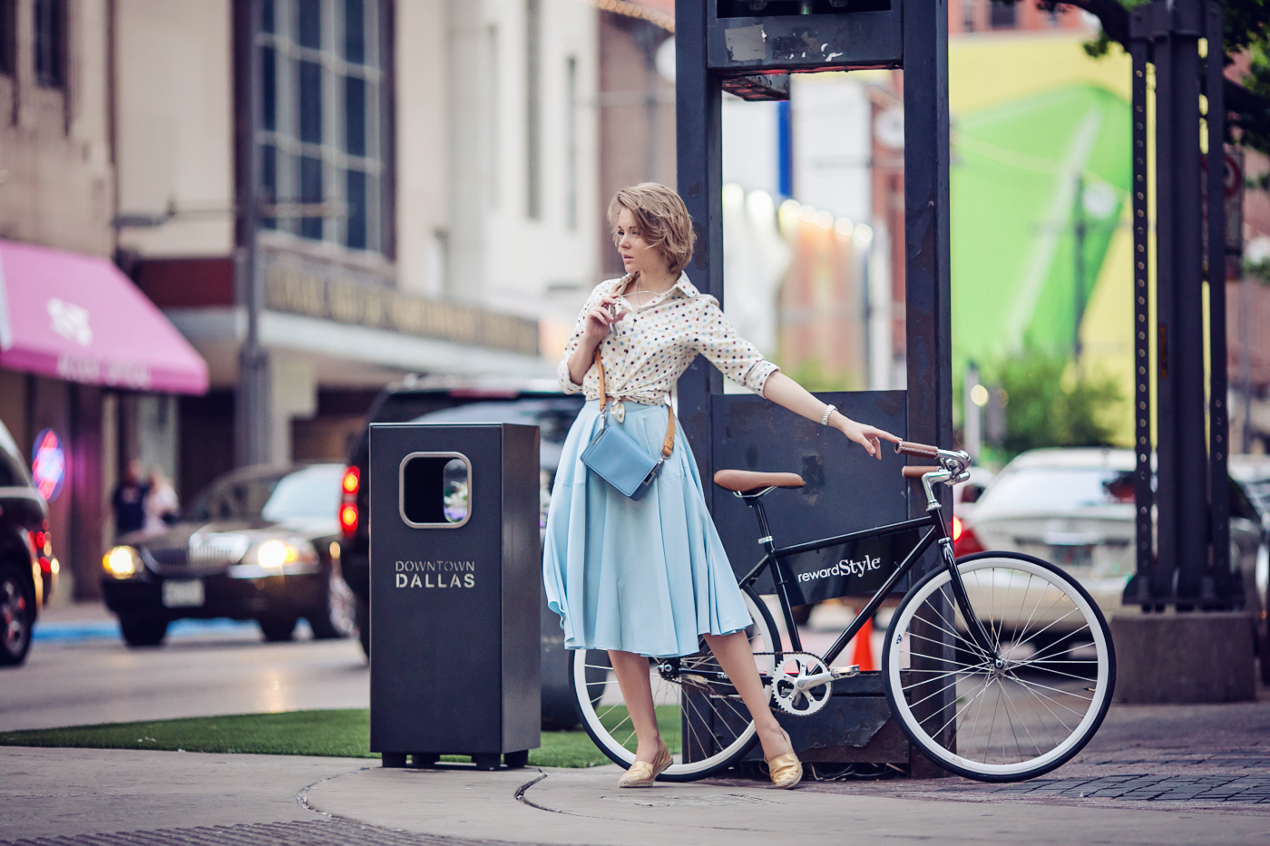 darya kamalova a fashion blogger from thecablook in dallas texas on the bycicle in polka dot shirt and blue skirt with gold espadrilles and other storie bag for rewardstyle rsthecon-18 copy