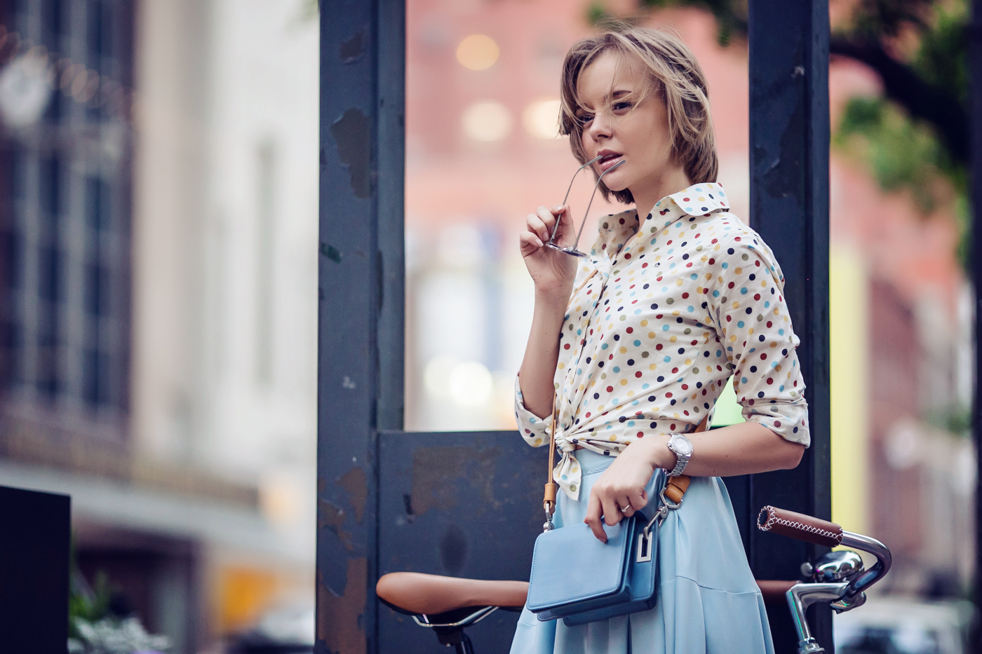 darya kamalova a fashion blogger from thecablook in dallas texas on the bycicle in polka dot shirt and blue skirt with gold espadrilles and other storie bag for rewardstyle rsthecon-19