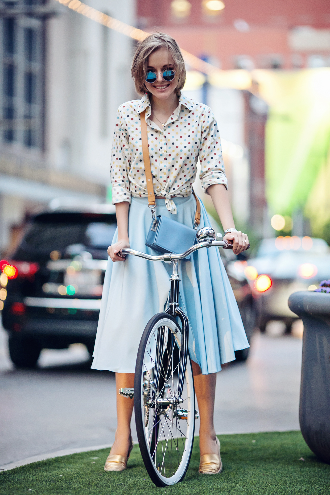 darya kamalova a fashion blogger from thecablook in dallas texas on the bycicle in polka dot shirt and blue skirt with gold espadrilles and other storie bag for rewardstyle rsthecon-30 copy