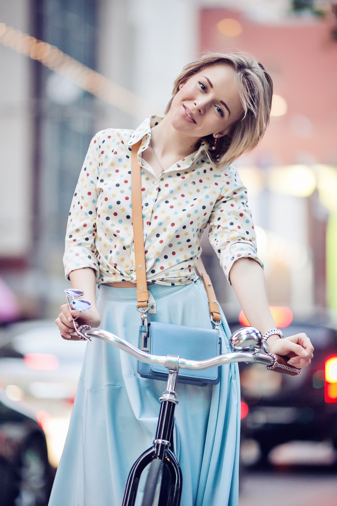 darya kamalova a fashion blogger from thecablook in dallas texas on the bycicle in polka dot shirt and blue skirt with gold espadrilles and other storie bag for rewardstyle rsthecon-40 copy
