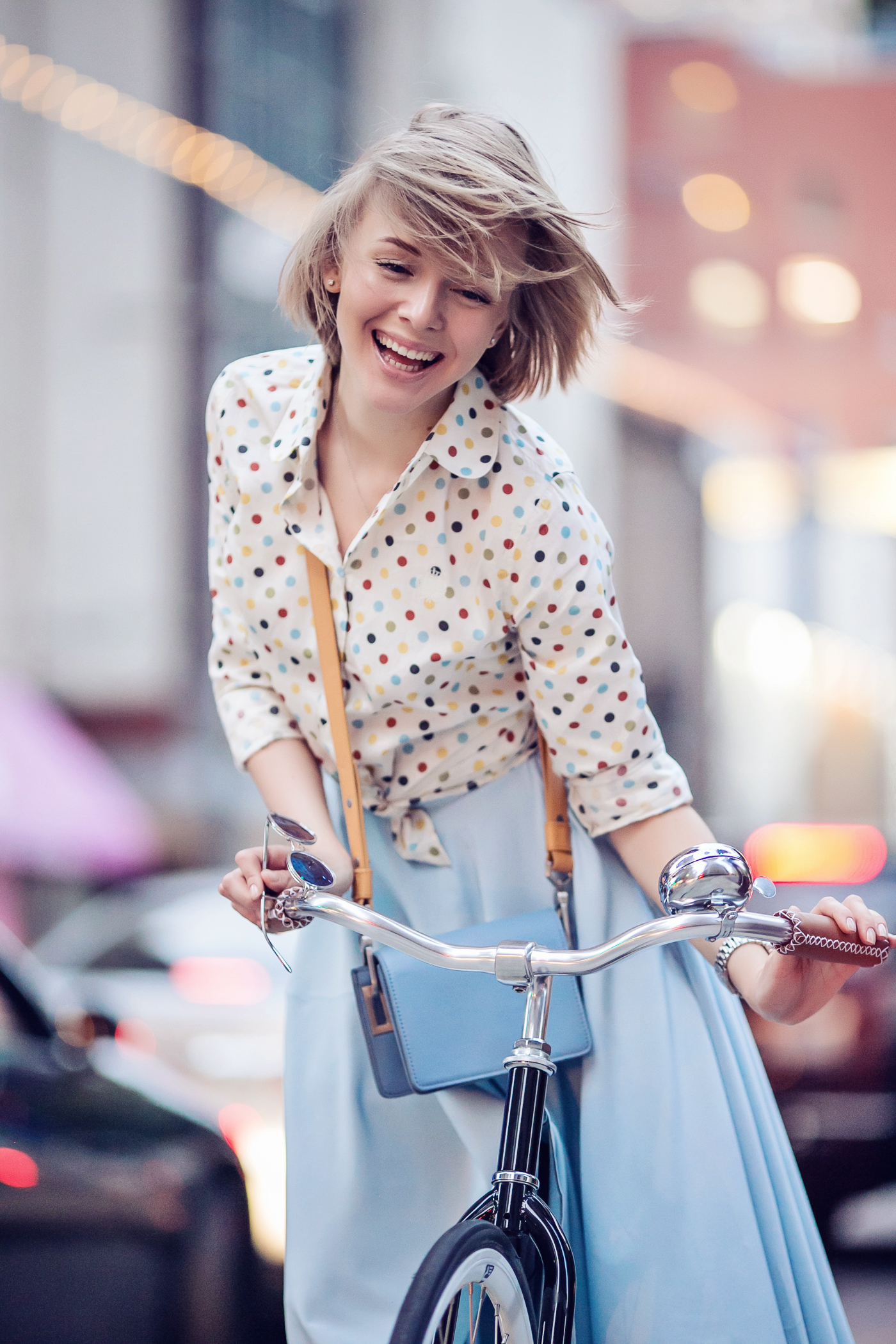 darya kamalova a fashion blogger from thecablook in dallas texas on the bycicle in polka dot shirt and blue skirt with gold espadrilles and other storie bag for rewardstyle rsthecon-48